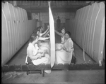 Female employees work on a wing section while military personnel watch at the Dayton-Wright Airplane Company