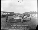 "Howard Rinehart standing beside the Dayton-Wright ""The Messenger"" at the Dayton-Wright Airplane Company South Field August 14, 1918"