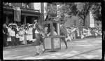 A Woman riding in a sedan chair during the 1909 Wright Brothers Homecoming Celebration parade