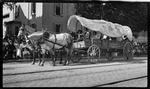 A covered wagon driving in the parade during the 1909 Wright Brothers Homecoming Celebration