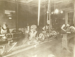 Interior view of Wright Cycle shop with workmen at lathes