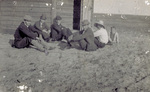 Group sitting on the sand outside camp building