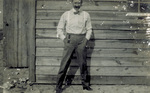 Orville Wright posing outside camp building