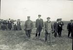 Spectators and aviators walk across flying field