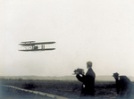 A photographer shooting the Wright Model A Flyer in flight
