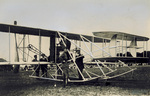 Orville Wright and an Army Officer stand near the Wright Model A Flyer
