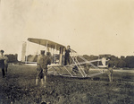 Orville Wright standing on machine making adjustments