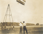 Wilbur Wright and Charlie Taylor watch the Wright 1909 Signal Corps Flyer at Fort Myer