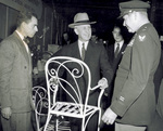 Orville Wright holding magnesium chair at Magnesium Show by U.S. Army Air Forces, Air Material Command