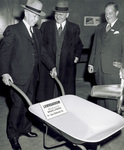 Orville Wright holding magnesium wheelbarrow at Magnesium Show by U.S. Army Air Forces, Air Material Command