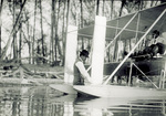Orville Wright standing in river with Wright Model CH Flyer