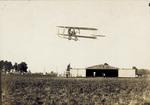Wright Model E Flyer in flight over Huffman Prairie hangar