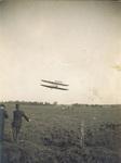 Two men watching Wright Model A Flyer in flight