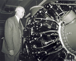Orville Wright examining an airplane engine