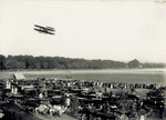 A large crowd watches the Wright Model A Flyer in flight