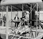 George H. Mannor sitting at the controls of a biplane at the Harvard-Boston Aero Meet, August - September, 1911