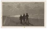 Three children standing on beach