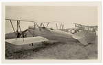 3/4 view of biplane in field